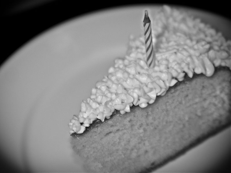 slice of birthday cake with candle